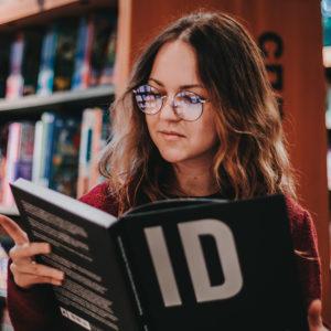 Frau liest Buch in Buchladen